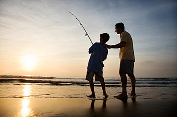 Fishing with Dad on the Beach at Sunset